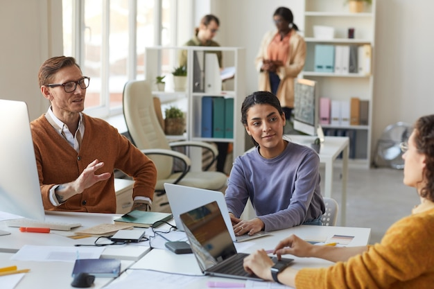 Retrato de equipo empresarial diverso que colabora en el proyecto mientras trabaja en la mesa en la sala de conferencias, espacio de copia