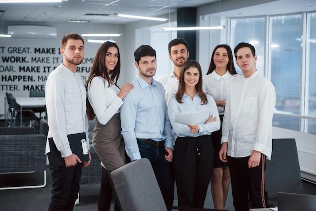 Retrato de equipo joven en ropa clásica en la moderna oficina bien iluminada