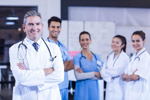 Retrato de equipo médico de pie con los brazos cruzados en el hospital