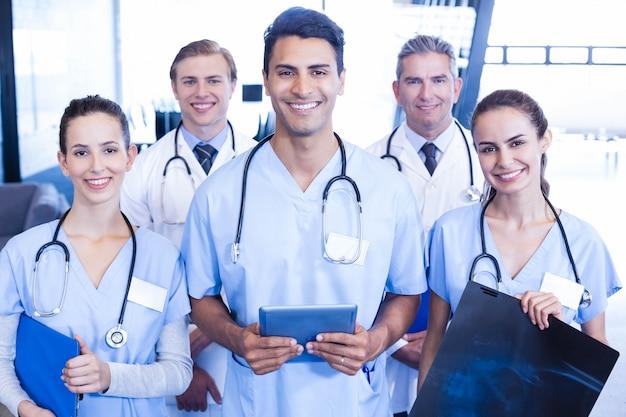 Retrato del equipo médico que se une y que sonríe en hospital