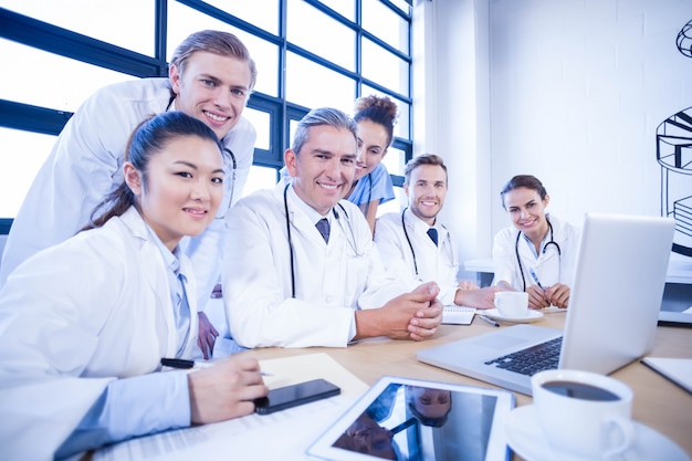 Retrato de equipo médico sonriendo en la sala de conferencias