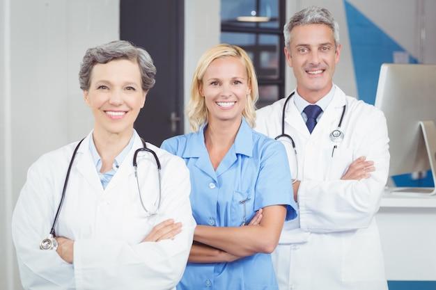 Retrato del equipo médico sonriente de pie con los brazos cruzados