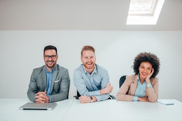 Retrato de un equipo millenial positivo del negocio que se sienta en sala de reunión brillante, sonriendo en la cámara.