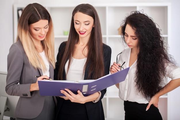 Retrato de equipo de mujeres empresarias felices de pie en el pasillo de la oficina, mirando a cámara, sonriendo.