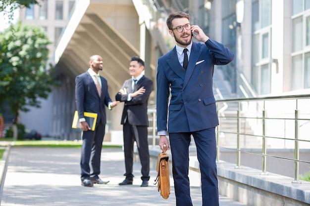 Retrato de equipo multiétnico de negocios. tres hombres de pie contra el fondo de la ciudad. el primer plano de un hombre europeo hablando por teléfono. otros hombres son chinos y afroamericanos.
