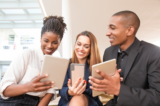 Retrato de equipo de negocios alegre usando tabletas y teléfono inteligente