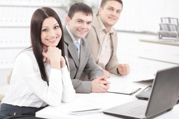 Retrato de equipo de negocios exitoso sentado en su escritorio.