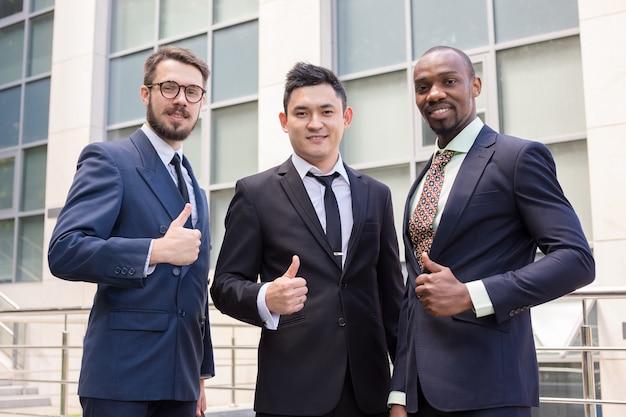 Retrato del equipo de negocios levantando los pulgares
