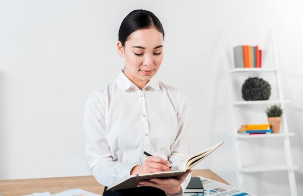 Retrato de una escritura asiática joven sonriente del hombre de negocios en el diario con la pluma