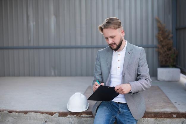 Retrato de la escritura hermosa joven del arquitecto en el tablero en el aire libre