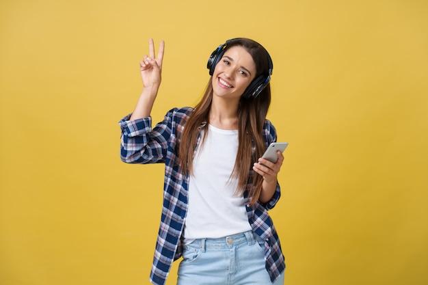 Retrato de escuchar alegre hermosa mujer caucásica a la música en el teléfono móvil.
