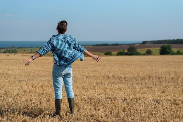 Retrato con la espalda de un hombre en jeans, camisa, botas de goma en el campo con las manos abiertas