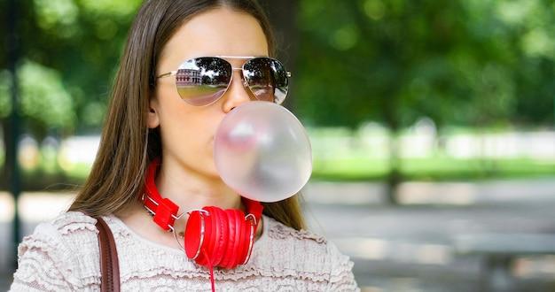 Retrato de estilo de vida al aire libre de hermosa mujer joven que sopla un globo de chicle