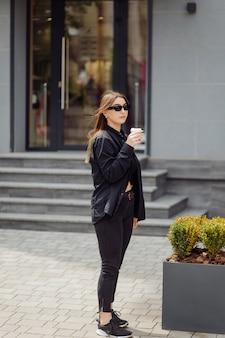 Retrato de estilo de vida al aire libre de la impresionante chica morena. tomando café y caminando por las calles de la ciudad.