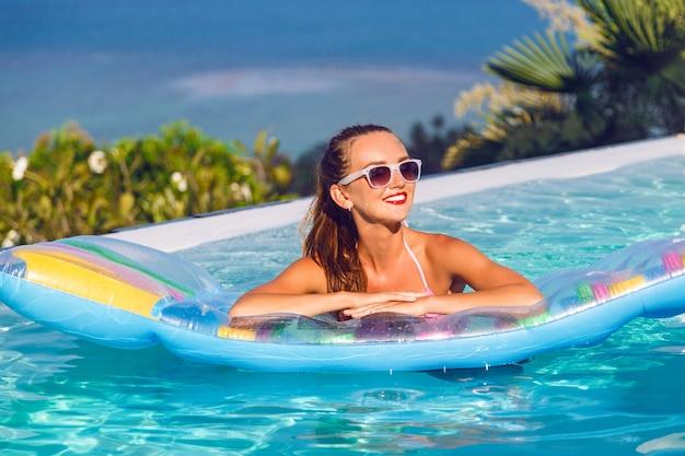 Retrato de estilo de vida al aire libre de impresionante joven divirtiéndose en la piscina infinita con impresionantes vistas a la isla tropical, vistiendo bikini brillante y gafas de sol, nadando en un colchón de aire.