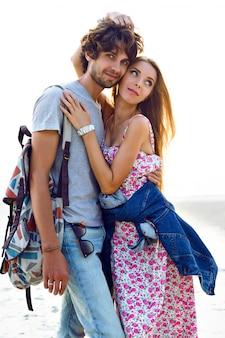 Retrato de estilo de vida al aire libre de una increíble pareja de enamorados posando en la playa. hombre y mujer con estilo se abrazan y pasan un buen rato juntos. mochila de vestido floral y denim.
