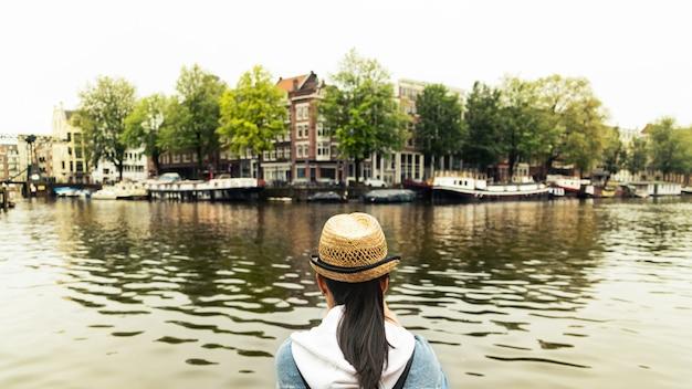 Retrato de estilo de vida al aire libre de una mujer joven y bonita divirtiéndose en la ciudad de europa con una cámara digital de fotos de viaje del fotógrafo hacer fotos en estilo hipster