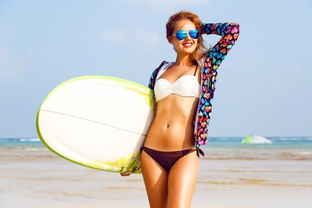 Retrato de estilo de vida al aire libre de surfista posando en la playa y sosteniendo la tabla de surf
