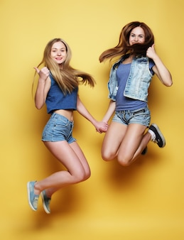 Retrato de estilo de vida de dos chicas jóvenes mejores amigos saltan sobre vosotros