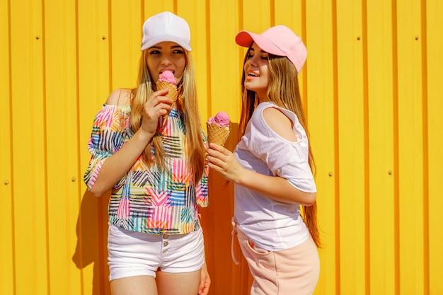 Retrato de estilo de vida de dos hermosas amigas hipster con elegantes trajes brillantes y divirtiéndose. parado cerca de la pared amarilla disfrutando del día libre y comiendo helado dulce y frío
