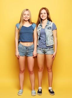 Retrato de estilo de vida de dos jóvenes amigas que saltan sobre ti