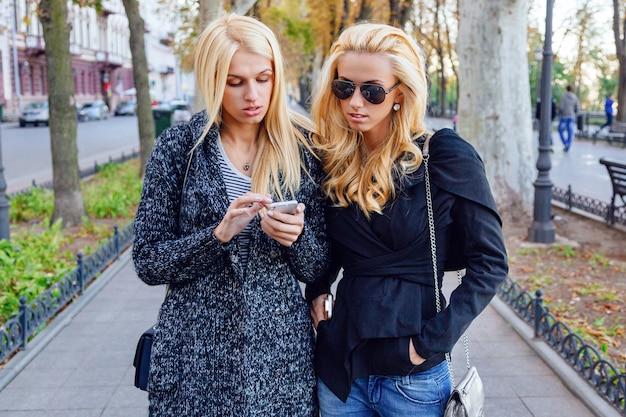 Retrato de estilo de vida de dos mejores amigas rubias que pasan tiempo en el centro de la ciudad en un bonito día de otoño otoño, con smartphone, con gafas de sol y looks de moda.