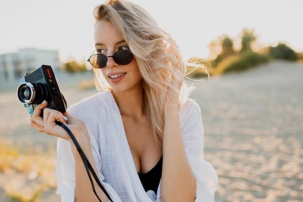 Retrato de estilo de vida de la elegante chica rubia divirtiéndose y haciendo fotos en la playa vacía. vacaciones y tiempo de vacaciones. libertad y naturaleza en el campo.