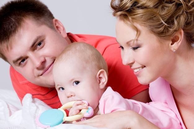 Retrato de estilo de vida de la hermosa joven familia feliz acostado en la cama en casa