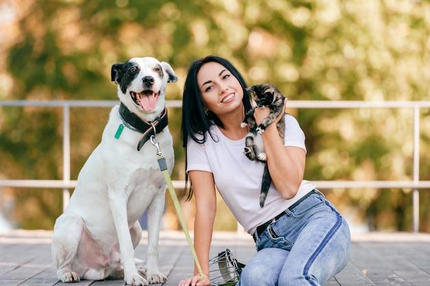 Retrato de estilo de vida de la hermosa joven morena con pequeño gato y perro de caza grande sentado al aire libre en el parque. feliz alegre sonriente adolescente abrazando encantadoras mascotas. propietario y amistad animales lindos