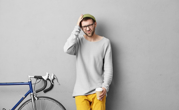 Retrato de estilo de vida del hombre joven de moda con barba con aspecto doloroso debido a dolor de cabeza, de pie aislado en la pared gris con bicicleta fija y sosteniendo la taza de papel, tomando café para llevar