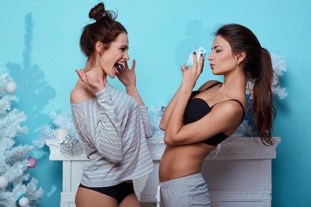 Retrato de estilo de vida interior de dos mejores amigas chicas locas hipster