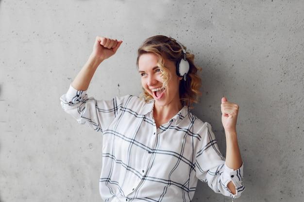 Retrato de estilo de vida interior de mujer entusiasta feliz escuchando música en una silla sobre fondo gris de la pared urbana.
