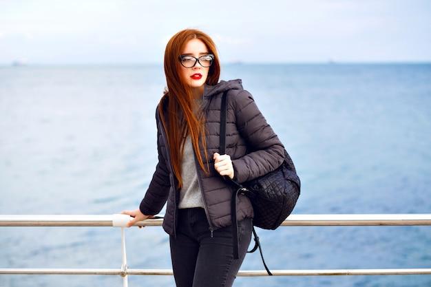 Retrato de estilo de vida de invierno de mujer de jengibre bastante hipster caminando en la playa, traje elegante negro total, clima frío y lluvioso, mochila, botas de cuero, solitario.