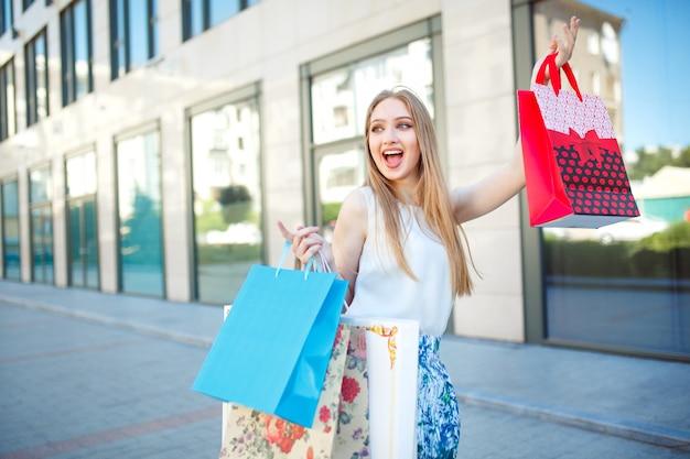 Retrato de estilo de vida joven rubia, con bolsas de compras saliendo de la tienda.