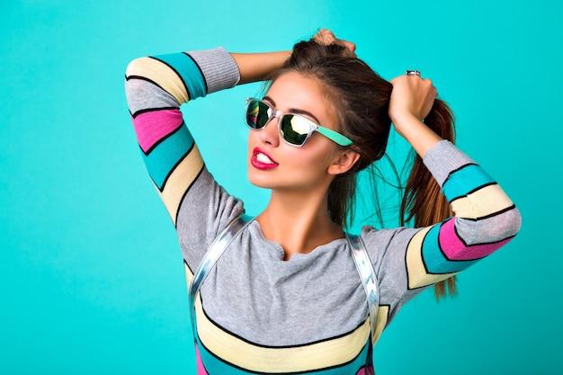 Retrato de estilo de vida de moda de mujer divertida alegre, labios carnosos sexy, gafas de sol espejadas, sosteniendo sus pelos como dos colas de caballo, colores primaverales, fondo de menta. emociones lindas, mujer de moda.