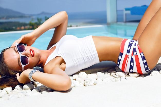 Retrato de estilo de vida de moda de mujer sexy con un cuerpo perfecto, relajado junto a la piscina en sus vacaciones, escuchando su música favorita en auriculares vintage, vistiendo un traje de verano brillante y gafas de sol.