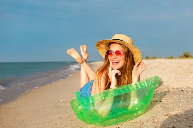 Retrato de estilo de vida de la mujer rubia de belleza feliz yacía en un colchón de aire tomando el sol en la playa, sonriendo y disfrutando de las vacaciones de verano