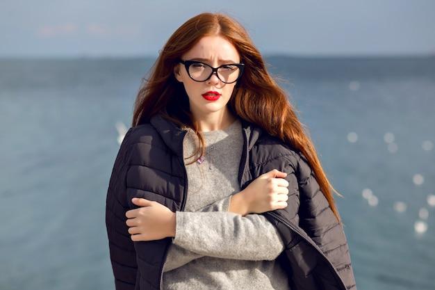 Retrato de estilo de vida de otoño al aire libre de mujer elegante caminando sola en la playa, vista increíble sobre el mar, viajar solo, moda callejera.