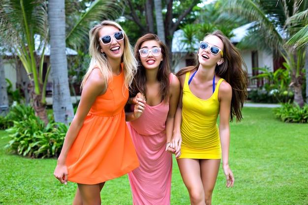 Retrato de estilo de vida tropical de verano de tres mejores amigas felices divirtiéndose al aire libre, vistiendo coloridos vestidos sexy, estilo de playa de fiesta de vacaciones, jardín exótico, ropa de moda, gafas de sol, relax, alegría