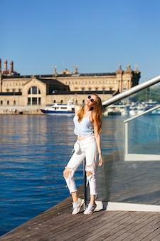 Retrato de estilo de vida de verano de mujer bonita rubia viaja sola en barcelona, hermosa arquitectura y vista al mar, look de estilo callejero de moda, vacaciones, alegría, viajero, top corto y denim.