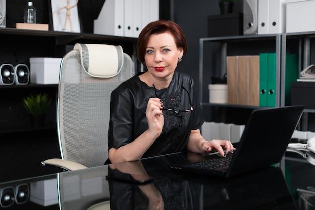 Retrato de estricta empresaria con laptop en elegante oficina