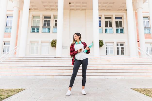Retrato del estudiante adolescente sonriente que sostiene los libros y la taza de café para llevar que se coloca delante del edificio de la universidad