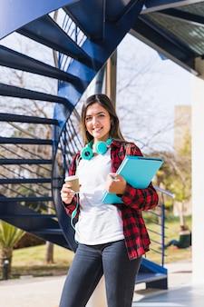 Retrato del estudiante adolescente sonriente que sostiene los libros y la taza de café para llevar que mira a la cámara