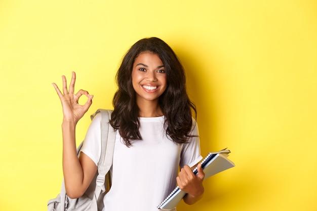 Retrato de estudiante afroamericana satisfecha, sonriendo complacida y mostrando signo bien, como algo bueno, de pie sobre fondo amarillo.