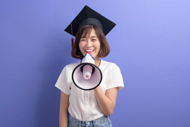 Un retrato de estudiante asiático graduado con megáfono aislado púrpura