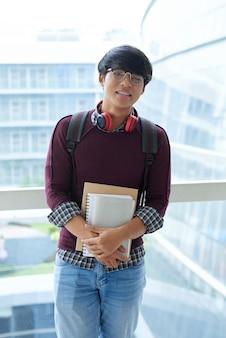 Retrato de un estudiante asiático posando con libros de estudio en el balcón de la escuela