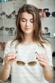 Retrato de estudiante bastante caucásico en tienda de óptica escogiendo un par perfecto de gafas de sol