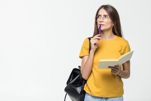 Retrato de una estudiante casual sonriente con mochila escribiendo en un bloc de notas mientras está de pie con libros aislados sobre la pared blanca
