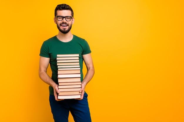Retrato de estudiante chico positivo mantenga pila libro de papel de pila