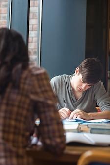 Retrato de un estudiante escribiendo un ensayo